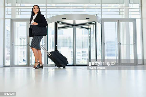 Businesswoman rolling luggage in lobby