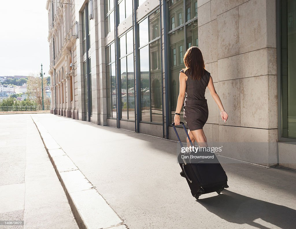 Businesswoman rolling luggage outdoors : Stock Photo