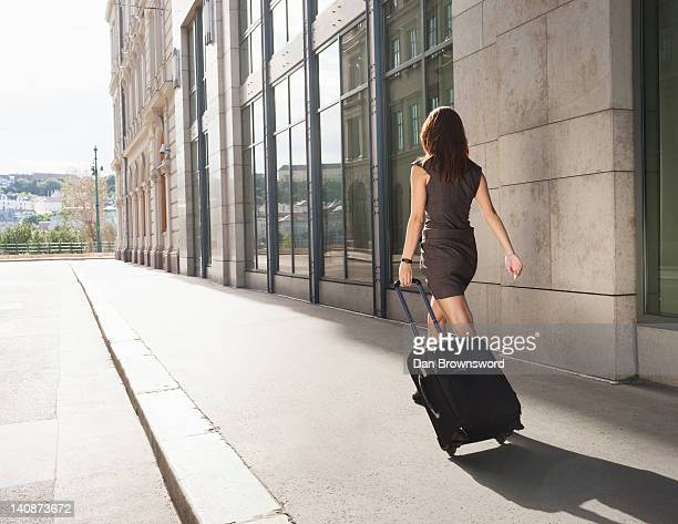 businesswoman rolling luggage outdoors - wheeled luggage stock photos and pictures