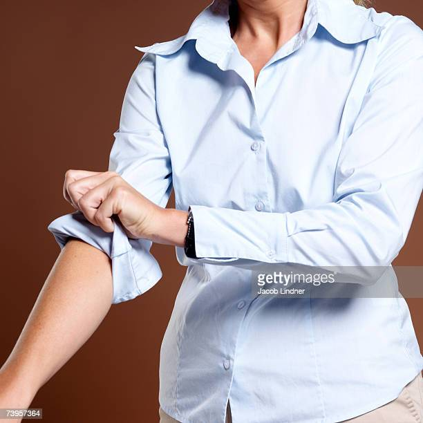 businesswoman rolling up shirt sleeves, close-up - de rola imagens e fotografias de stock