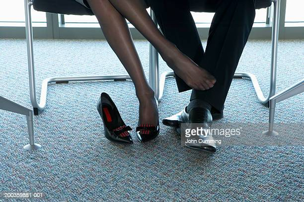 businesswoman rubbing businessman's leg with foot, low section - nylon feet stock photos and pictures