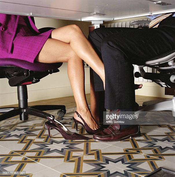 Businesswoman rubbing foot against businessman's leg, low section