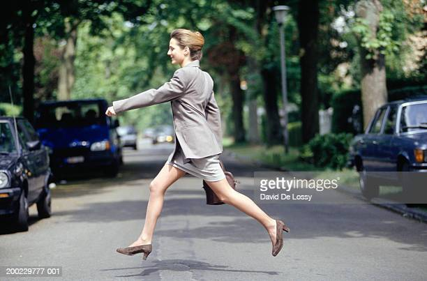 Businesswoman running across road, side view
