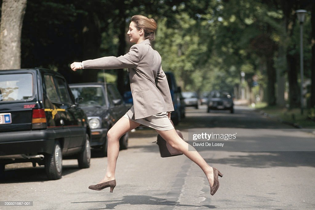 Businesswoman running across road, side view : Foto de stock