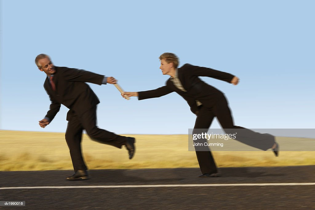 Businesswoman Running and Passing a Relay Baton to a Businessman on a Country Road : Stock Photo