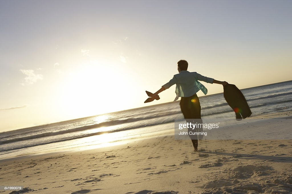 Businesswoman Running Barefoot on the Beach Towards the Sea : Stock Photo
