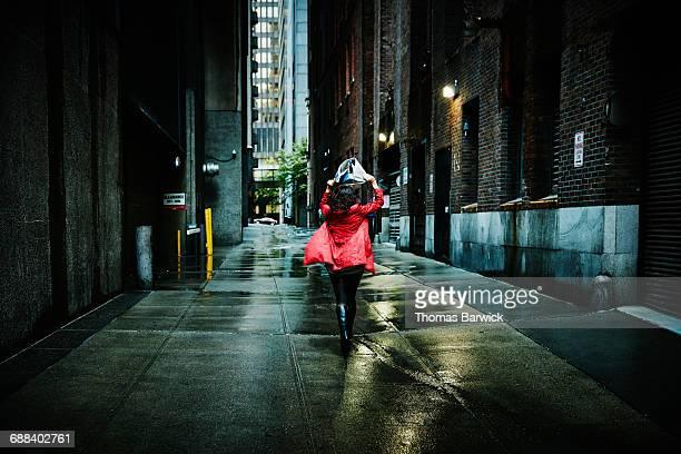 Businesswoman running down alley in rain storm