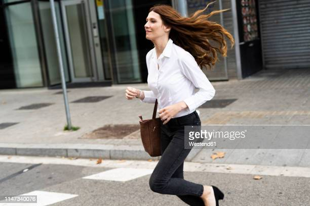 businesswoman running in the street - dringendheid stockfoto's en -beelden