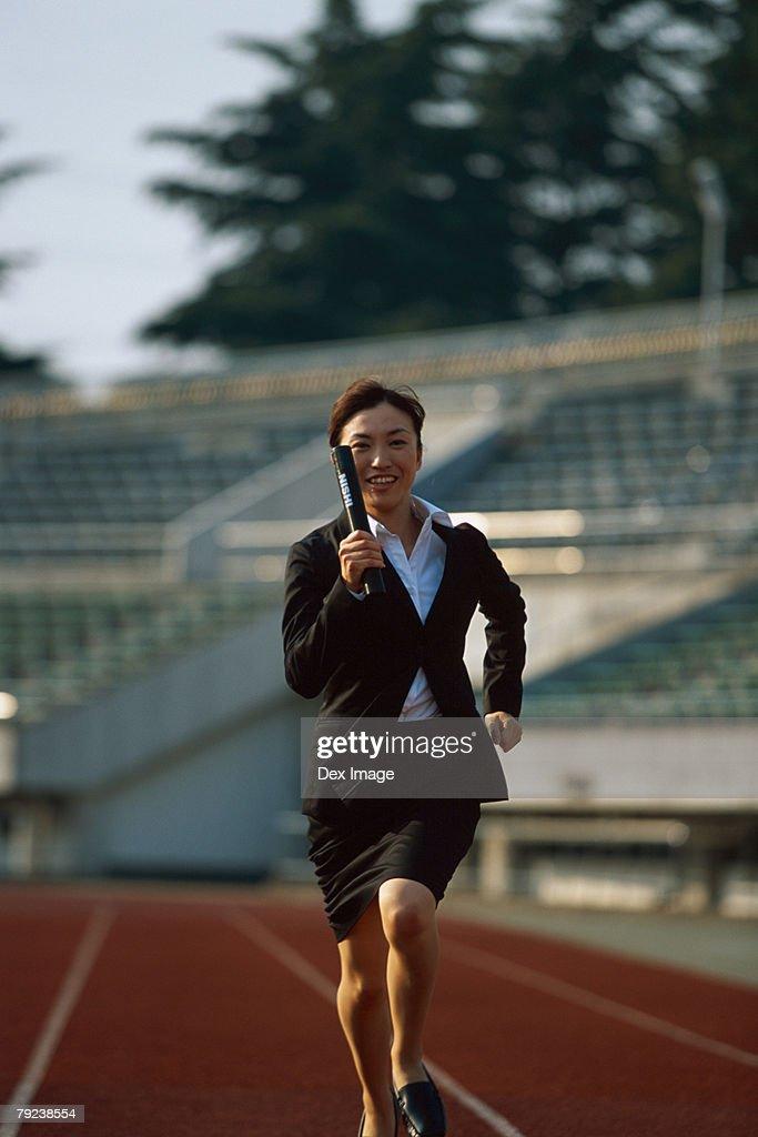 Businesswoman running relay race : Stock Photo