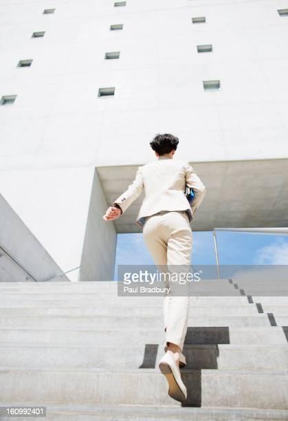 Businesswoman rushing up urban stairs