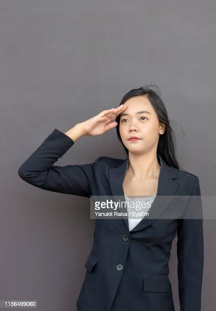 businesswoman saluting against gray background - 敬礼 ストックフォトと画像