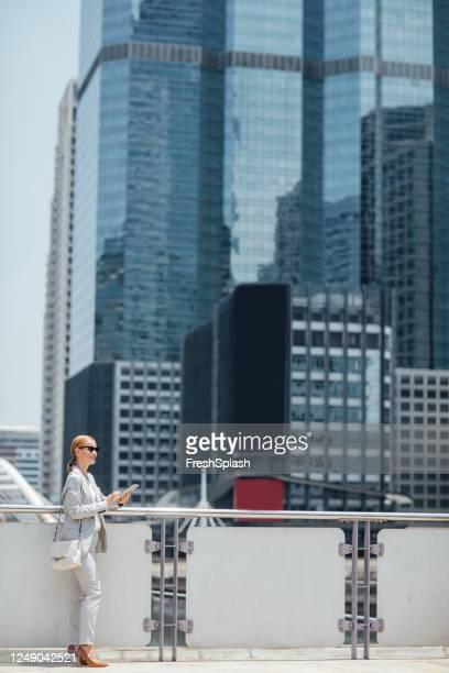 businesswoman satnding by the city skyscrapers - pump dress shoe stock pictures, royalty-free photos & images