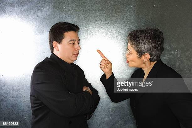 Businesswoman scolding businessman