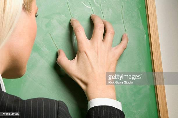 Businesswoman Scraping Fingernails Across Blackboard