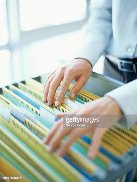 businesswoman searching files in a filing cabinet in an office