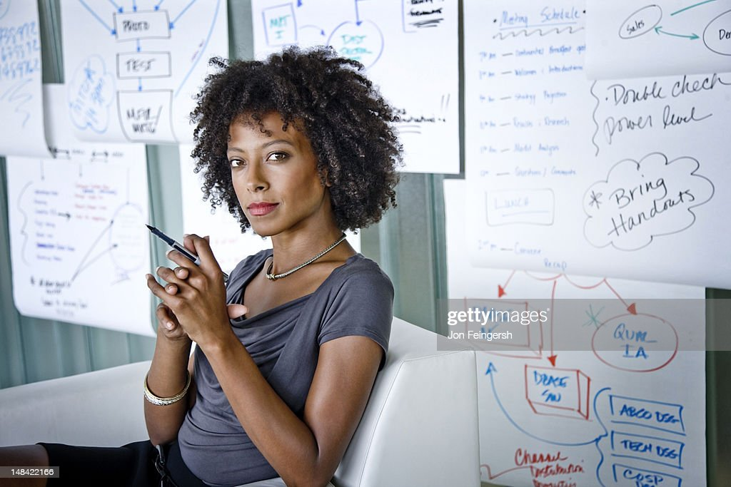Businesswoman seated with charts : Stock Photo