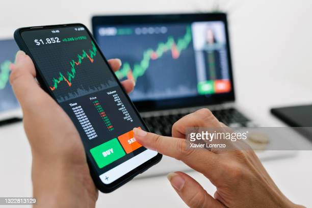 businesswoman selling cryptocurrencies through a mobile app - stock price stock pictures, royalty-free photos & images