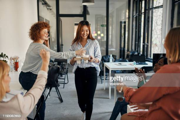 businesswoman serving coffee to colleagues in office - colleague stock pictures, royalty-free photos & images