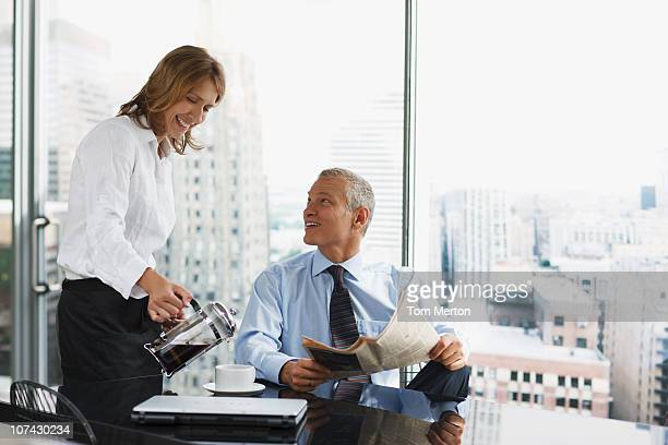 Businesswoman serving co-worker coffee in office