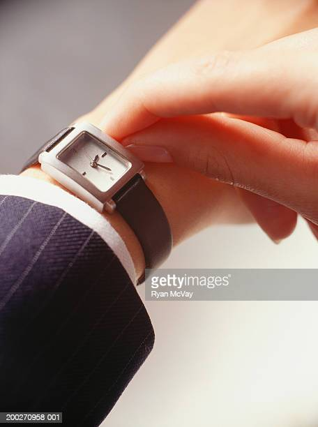 businesswoman setting watch, close-up of hand - strap stock pictures, royalty-free photos & images