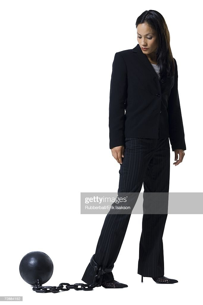 Businesswoman shackled to ball and chain : Stock Photo