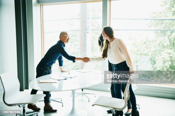 businesswoman shaking hands with client before meeting in office conference room - vinculación fotografías e imágenes de stock