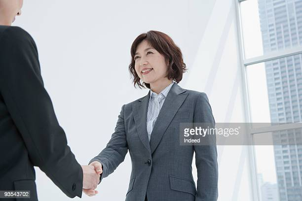 Businesswoman shaking hands with person off camera