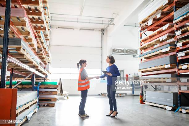 businesswoman shaking hands with worker in large warehouse. manager and worker handshake in storehouse - direttrice foto e immagini stock