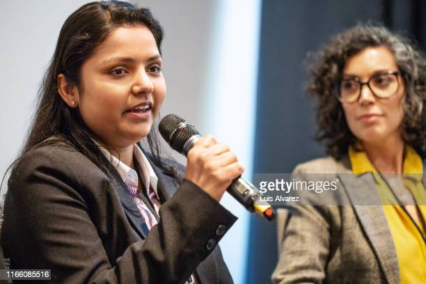 businesswoman sharing her views during a group discussion - panel discussion stock pictures, royalty-free photos & images