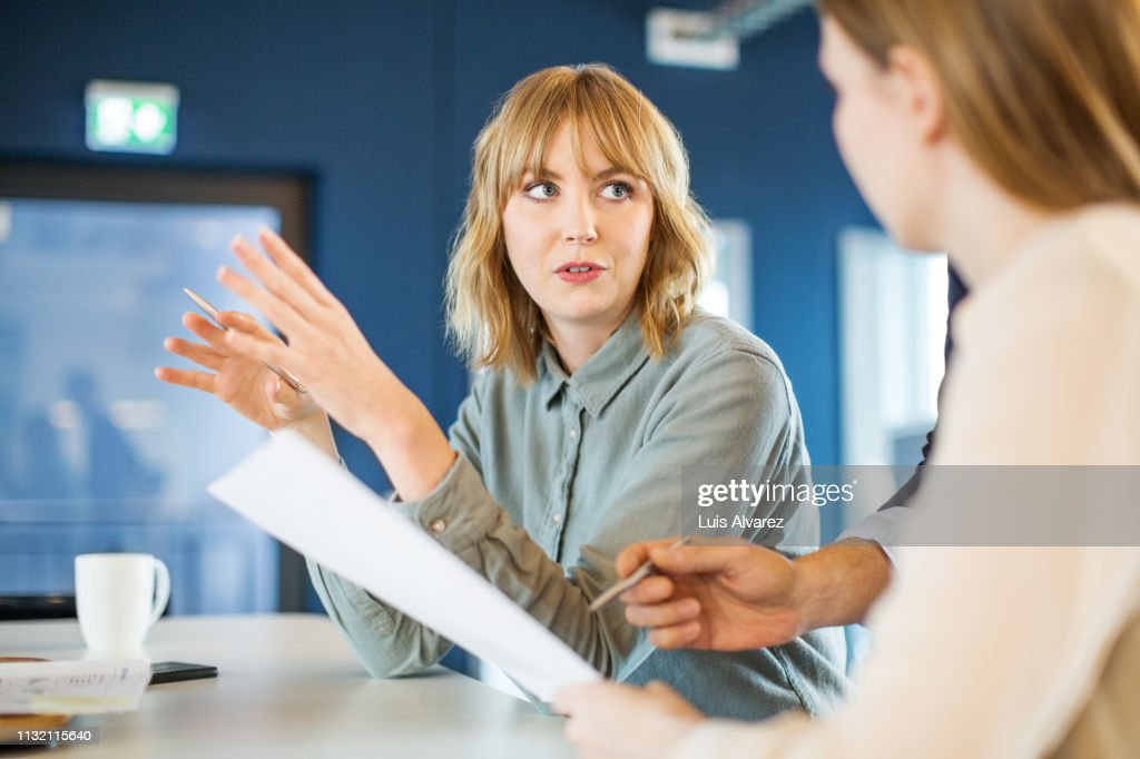 Businesswoman sharing ideas with colleague in meeting : Photo