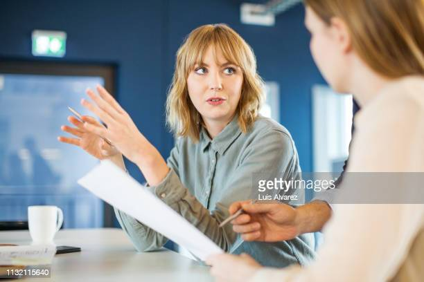 businesswoman sharing ideas with colleague in meeting - witte boorden werker stockfoto's en -beelden