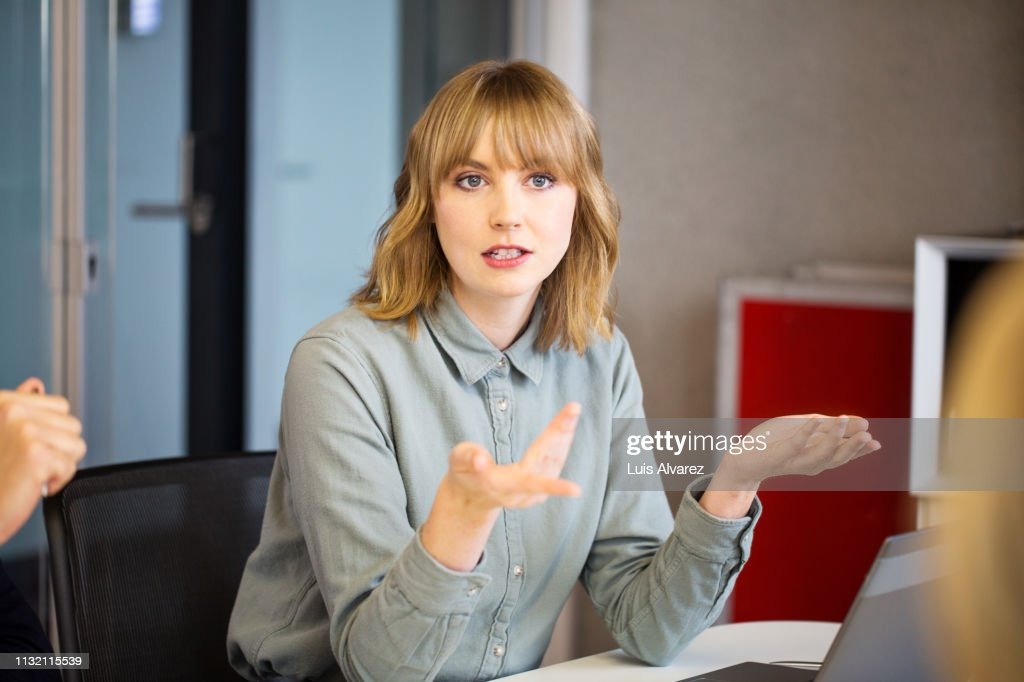 Businesswoman sharing ideas with colleagues : Photo