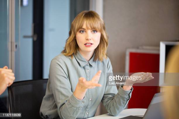 businesswoman sharing ideas with colleagues - gesturing stock pictures, royalty-free photos & images