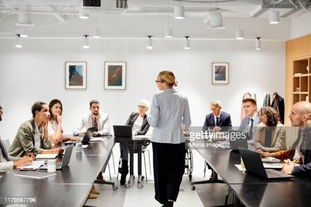 businesswoman sharing ideas with colleagues - grupo grande de personas fotografías e imágenes de stock