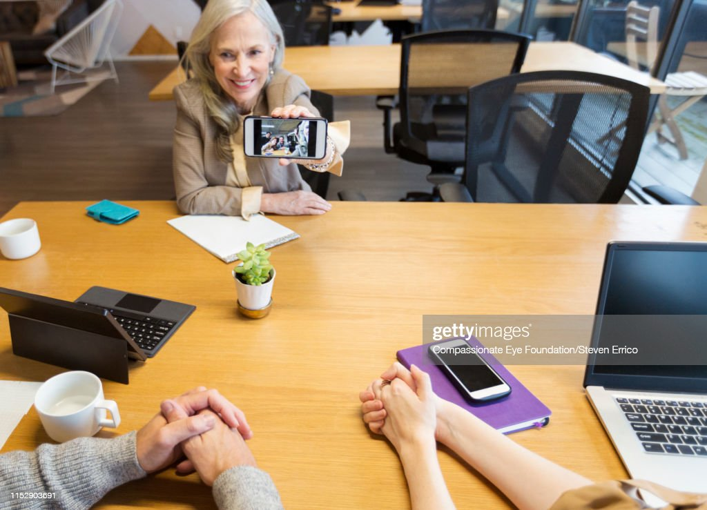 Businesswoman sharing selfie with co-workers in open plan office : Stock Photo