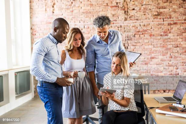 Businesswoman sharing tablet colleagues at desk in office