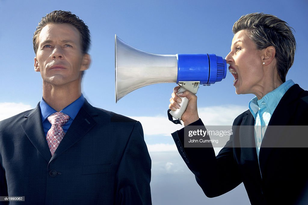 Businesswoman Shouting at a Businessman Through a Megaphone : Stock Photo