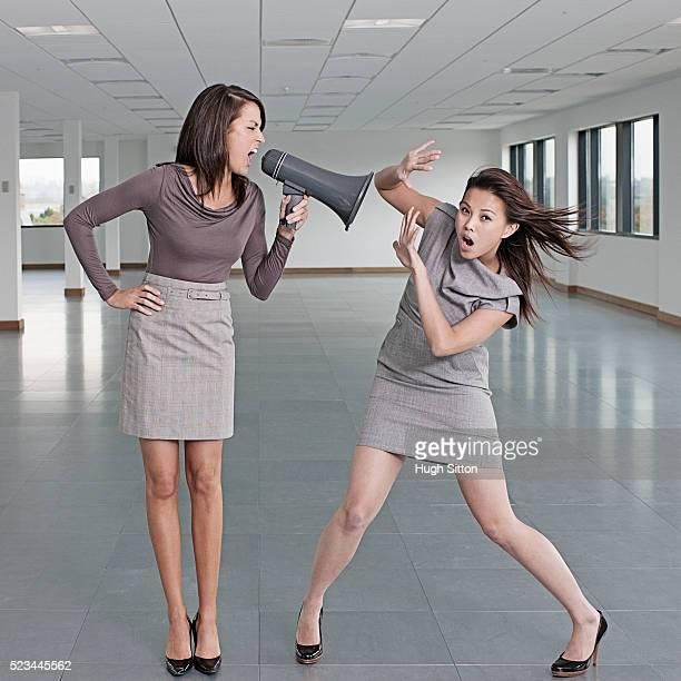 businesswoman shouting at colleague using megaphone - hugh sitton stock-fotos und bilder