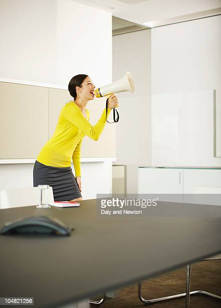 Businesswoman shouting in bullhorn in conference room