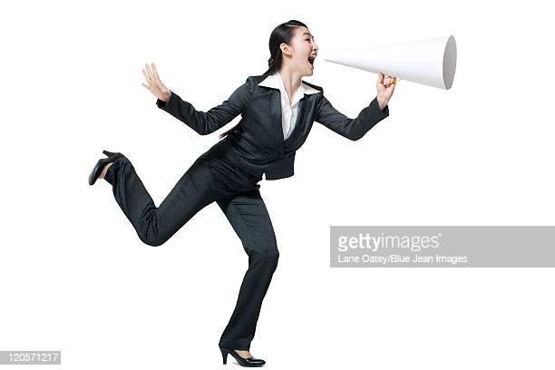 A businesswoman shouting into a megaphone