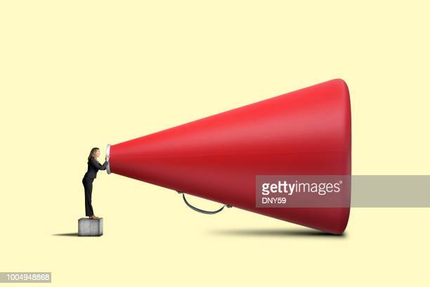 businesswoman shouts into very large red megaphone - communication problems stock pictures, royalty-free photos & images