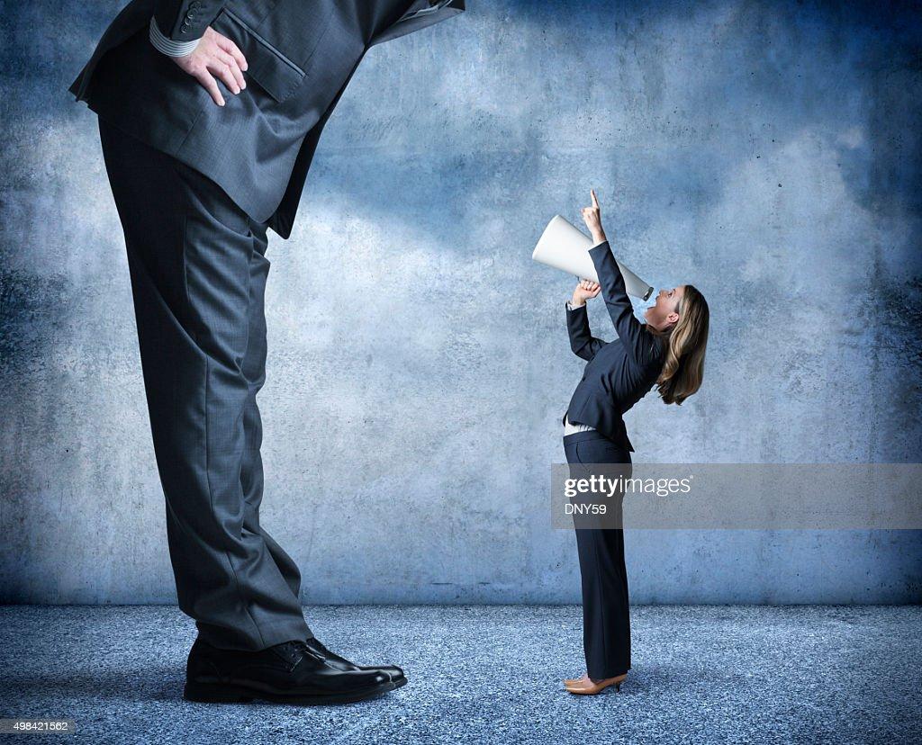Businesswoman Shouts Through Megaphone Towards Much Larger Businessman : Stock Photo
