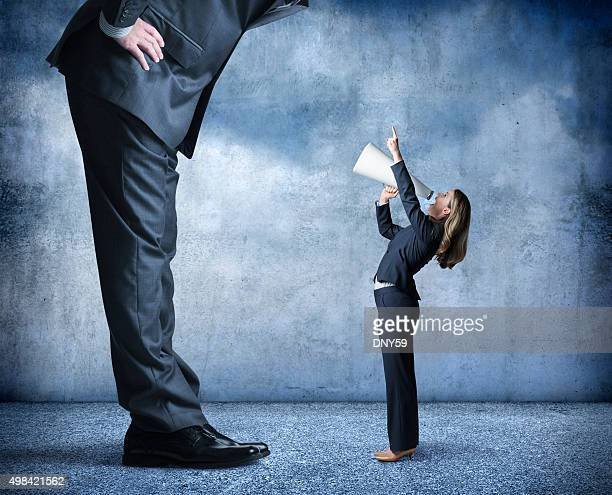 Businesswoman Shouts Through Megaphone Towards Much Larger Businessman