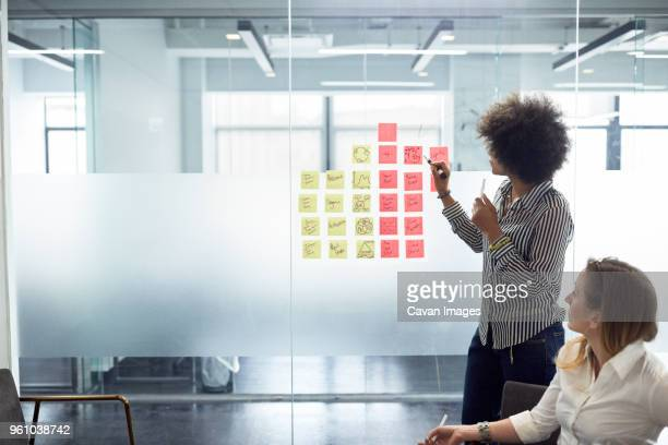businesswoman showing adhesive notes on glass wall to female colleague in office - business plan stock pictures, royalty-free photos & images