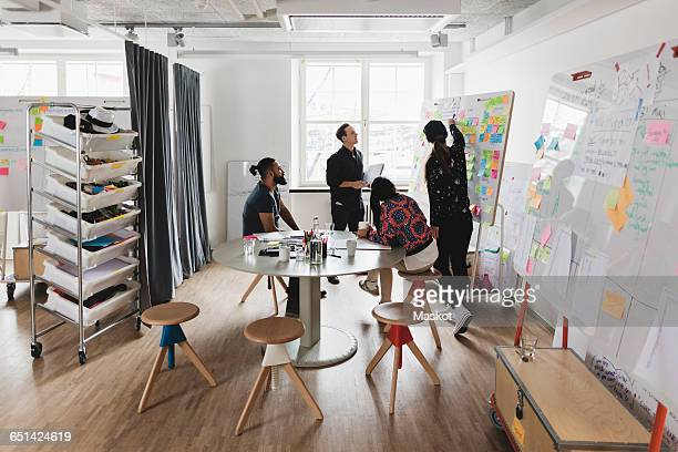 businesswoman showing colleagues note on whiteboard during meeting in board room - brainstorming stock pictures, royalty-free photos & images