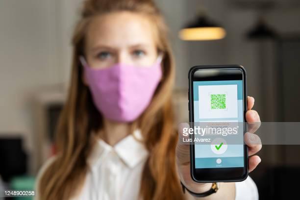businesswoman showing corona virus tracking app on her phone - exposição - fotografias e filmes do acervo
