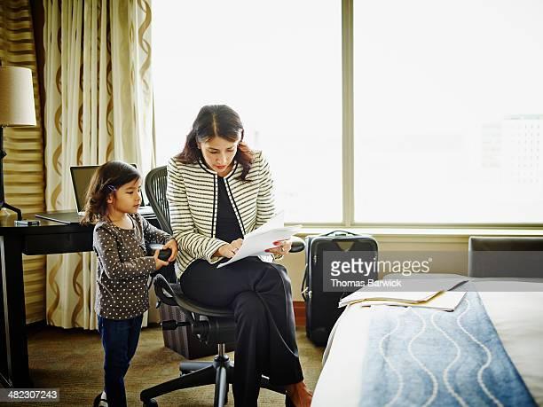 Businesswoman showing daughter paperwork in hotel