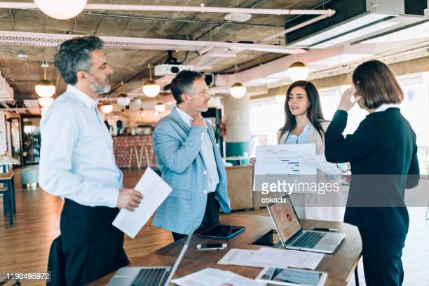 businesswoman showing sales leads to coworkers - pbs stock pictures, royalty-free photos & images