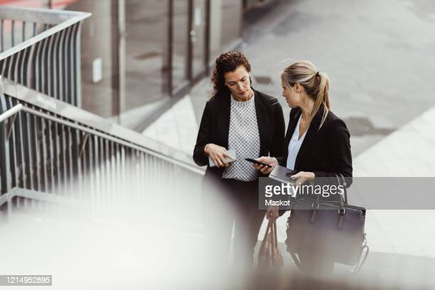 businesswoman showing smart phone to female colleague while discussing on steps - formal businesswear stock pictures, royalty-free photos & images