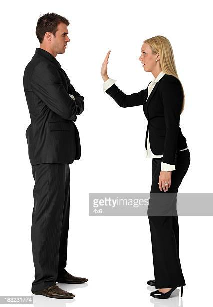 Businesswoman showing stop gesture in front of businessman